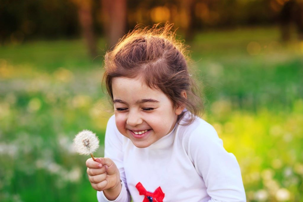 A little girl smiling while holding a dandelion
