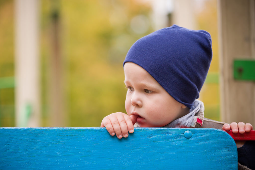 a child looking away at a playground