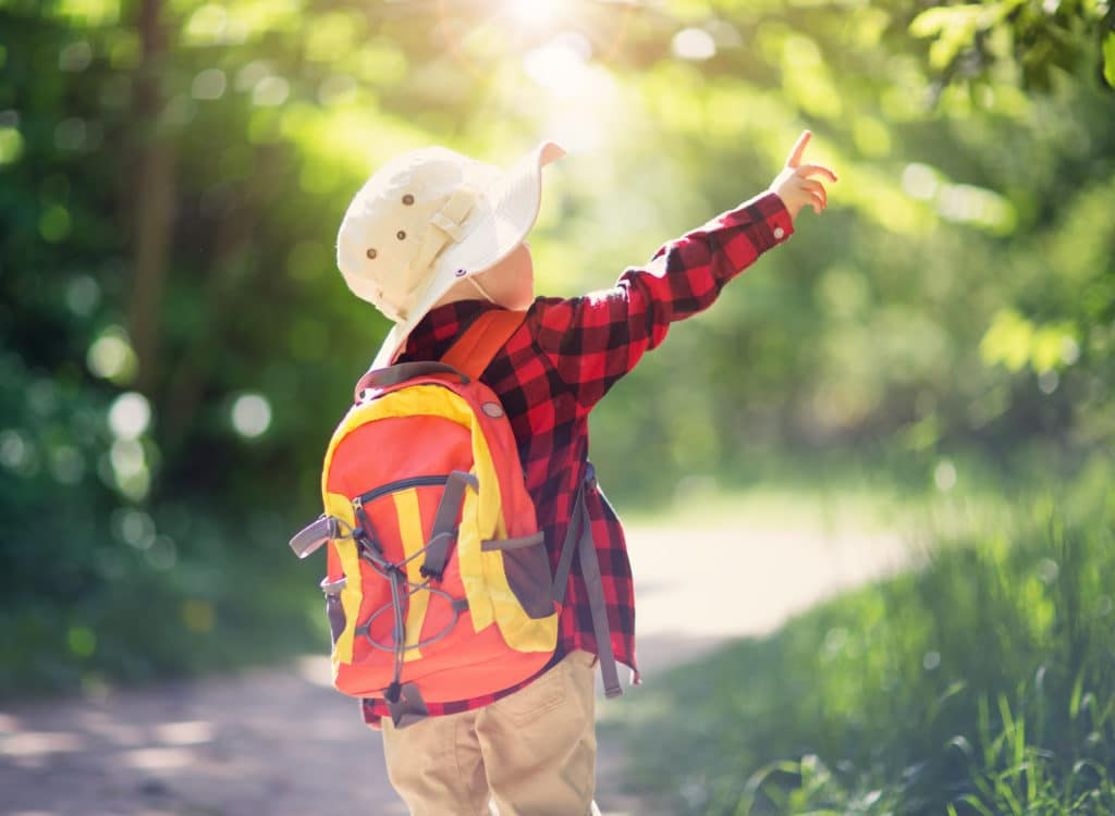 a young child in a forest path with a backpack and hat
