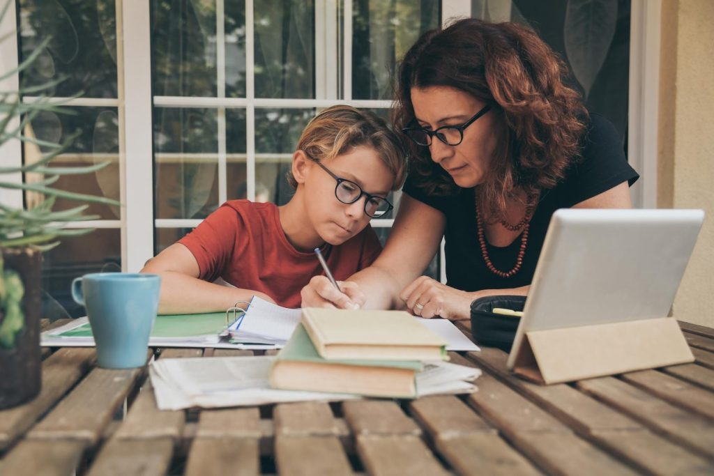 A young boy and his mother studying from home and doing homework